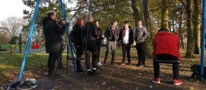 Young people in a park being filmed